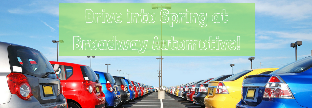 """cars on car dealership lot with text """"drive into spring at broadway automotive"""" above it"""