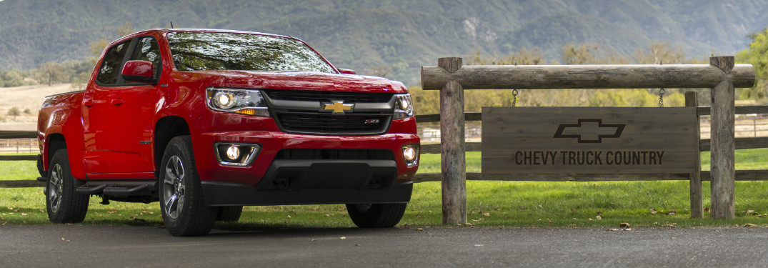 "red 2018 chevy colorado on ranch road next to wooden sign that says ""chevy country"""