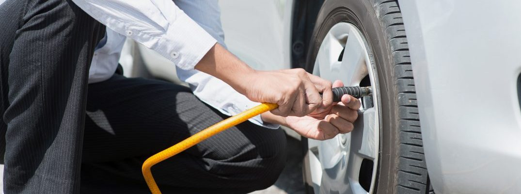 driver checking air pressure in tires