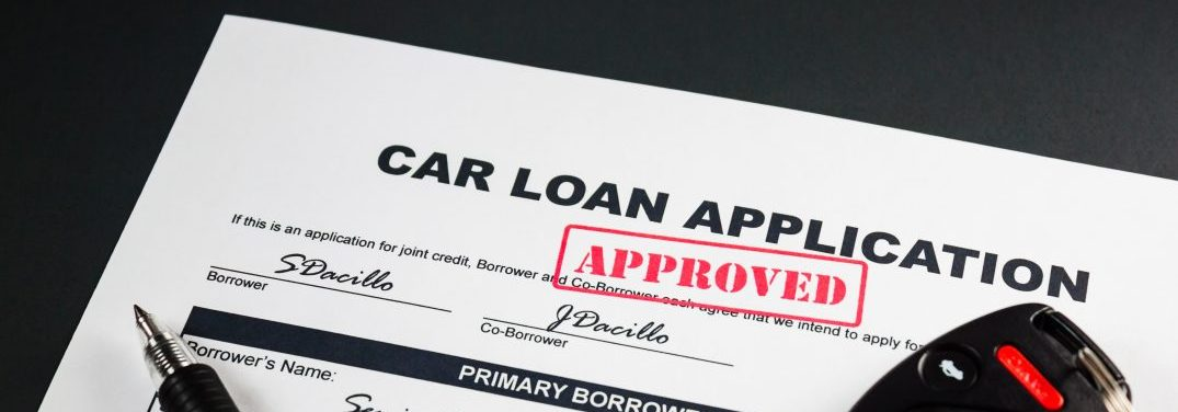 Filled-up car loan application form with approved stamp pen and a remote car key
