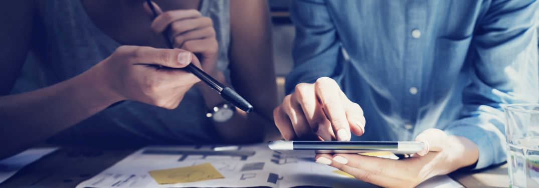man and woman studying tablet with papers and notes strewn around