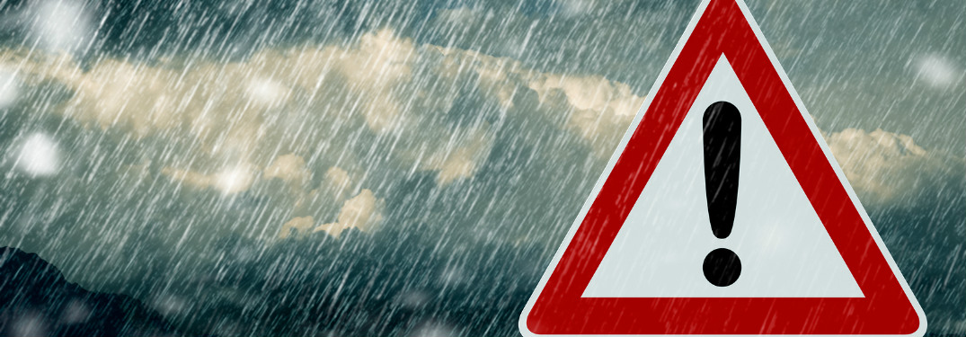 traffic sign with exclamation point with rain and storm clouds behind it