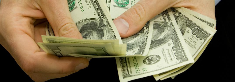man holding hundred dollar bills cash