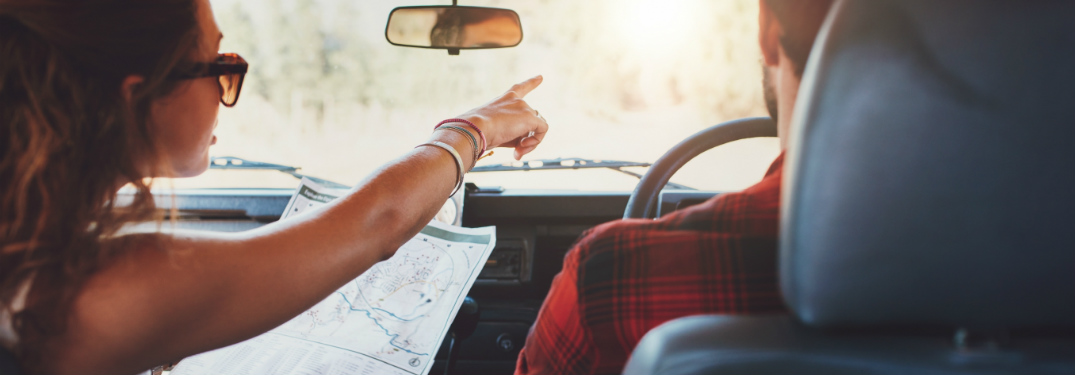 woman holding map in passenger seat and point for man driving
