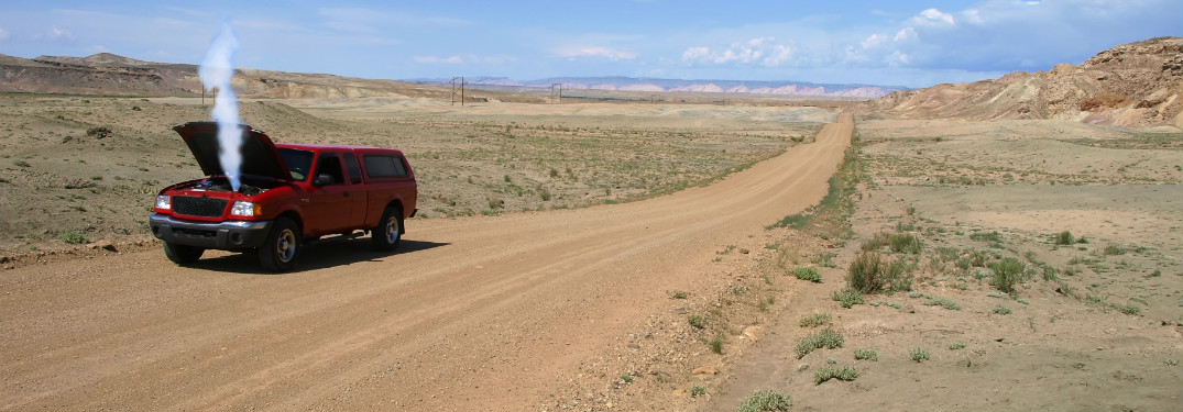 red suv on side of dirt road in empty desert with hood up and smoke coming out