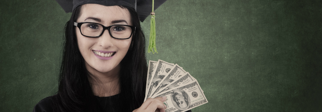 young woman in cap and gown holding cash dollar bills