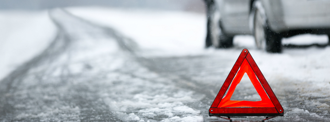 close up of orange triangle road hazard sign with car in snow in background