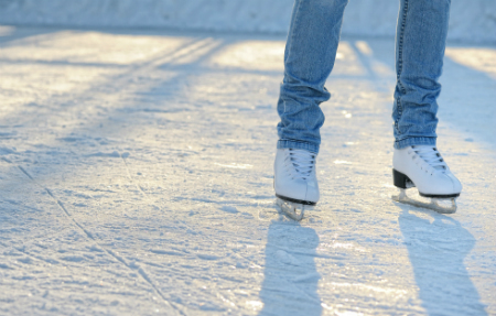 person's feet ice skating on rink