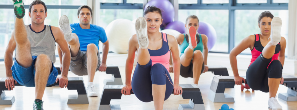 group of young people in workout class doing exercise together