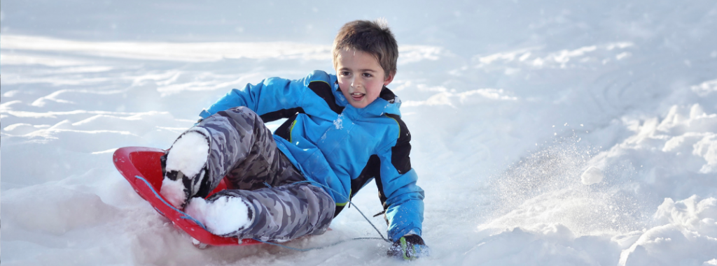 young boy sledding down hill on red sled
