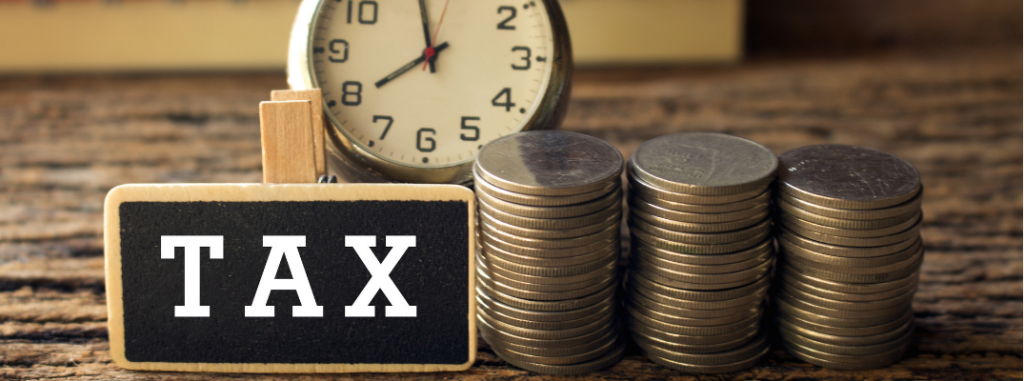 """clock and stacked coins next to plaque that says """"tax"""""""