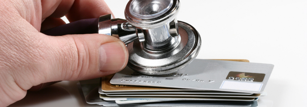 man's hand holding stethoscope on pile of credit cards