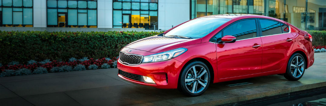 red 2018 kia forte in front of industrial university style building