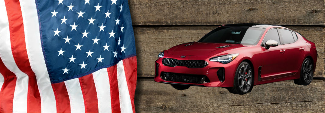 2018 Kia stinger alongside Ameircan flag on wood background