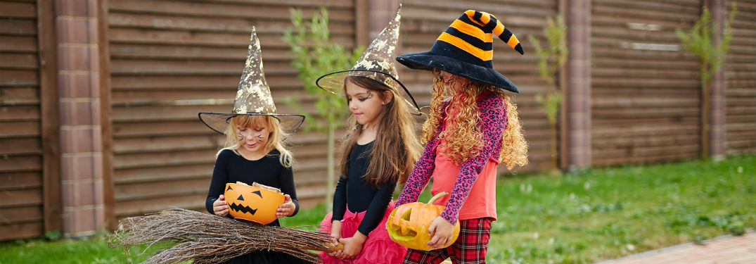 Girls in witch costumes trick or treating