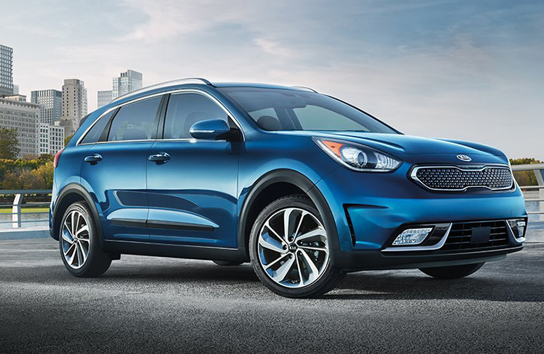 blue 2019 kia niro parked in front of city skyline