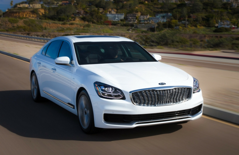 white 2019 kia k900 driving on street
