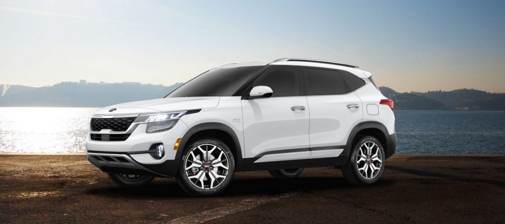 2021 kia seltos suv against oceanside background in snow white pearl