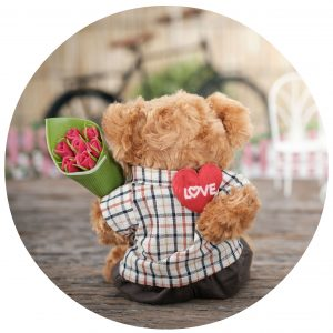 Teddy bear holding flowers and heart behind its back