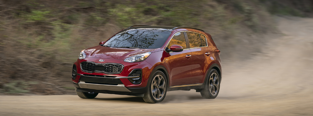 Red 2020 Kia Sportage driving in dirt