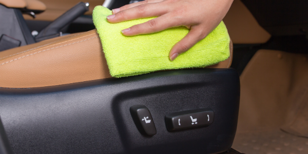 Hand cleaning interior of vehicle