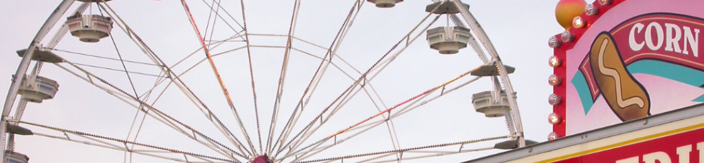 Closeup of ferris wheel and corn dog sign at county fair