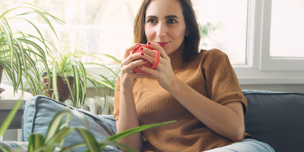 Woman holding mug and sitting on couch