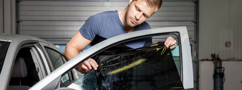 Man applying tint to vehicle window