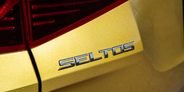 Closeup of badge on yellow 2021 Kia Seltos