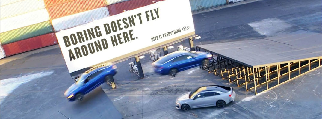 """Three Kia K5 vehicles performing Triple Threat Stunt with """"Boring Doesn't Fly Around Here"""" sign"""