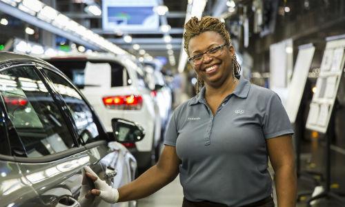 Kia Motors team member smiling and posing by vehicle