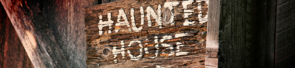 Closeup of wooden haunted house sign