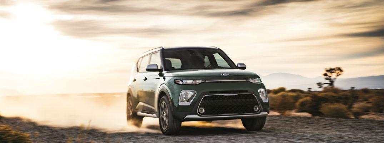 Green 2021 Kia Soul driving through dust
