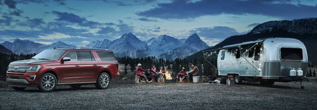 2018 Ford Expedition and Camper in Front of Mountains