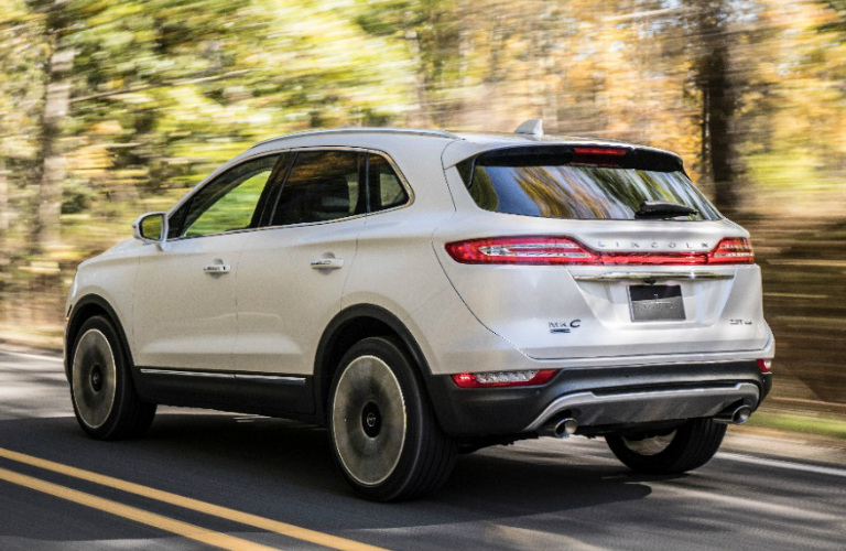 White 2019 Lincoln MKC Driving by a Forest