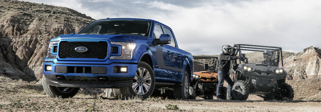 Blue 2018 Ford F-150 Parked next to ATVs