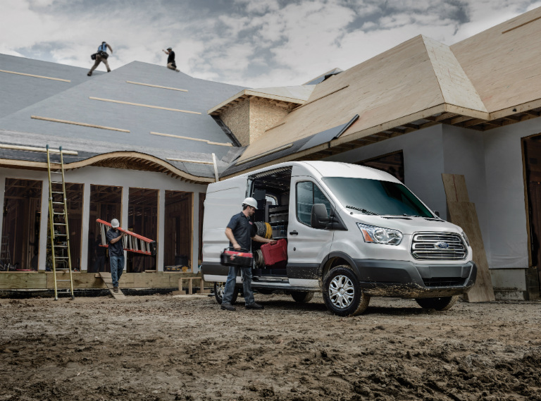 White 2018 Ford Transit 150 Medium-roof Cargo Van Parked by a House Construction Site