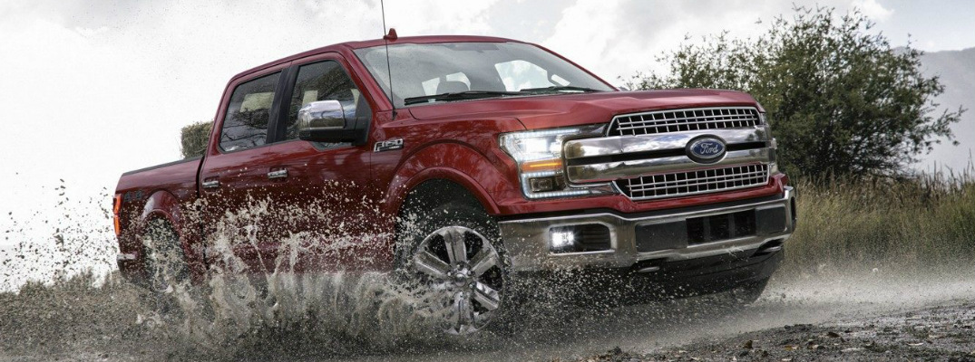 Red 2018 Ford F-150 Driving Through a Puddle