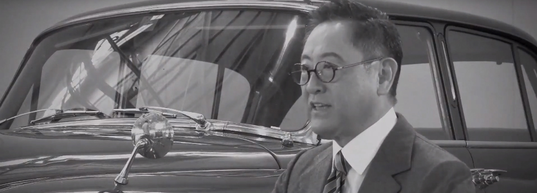 Toyota Founder Kiichiro Toyoda Sitting Next to a Toyota Car