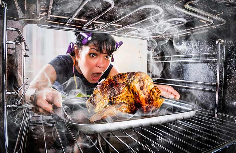 A Woman Taking Turkey out of the Oven