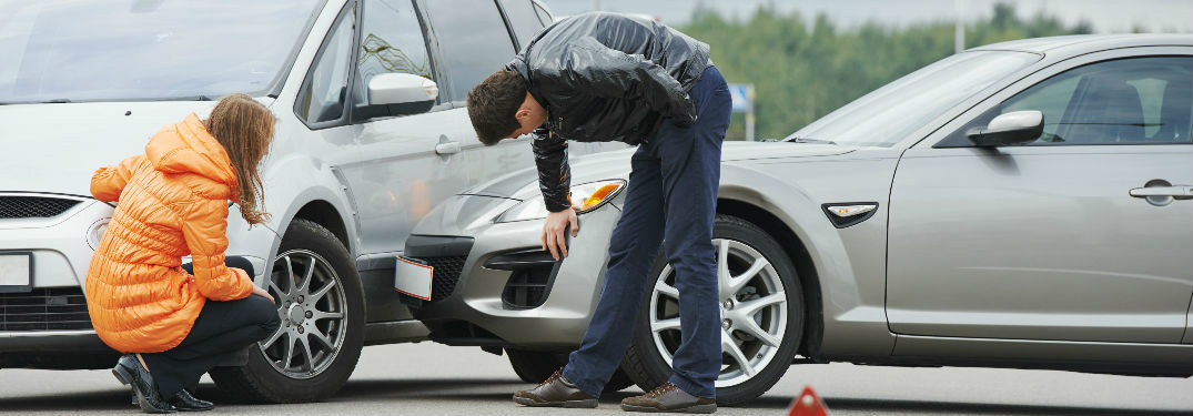 two drivers looking at damaged cars after colliding