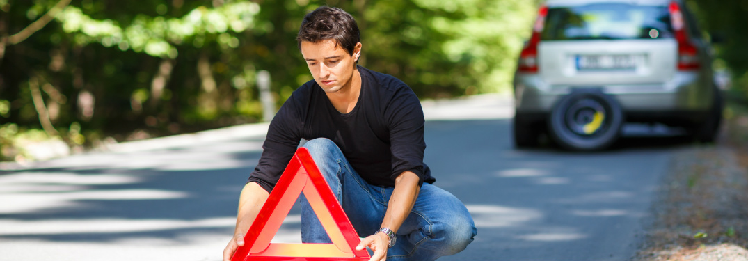 man setting up road triangle behind broken-down vehicle