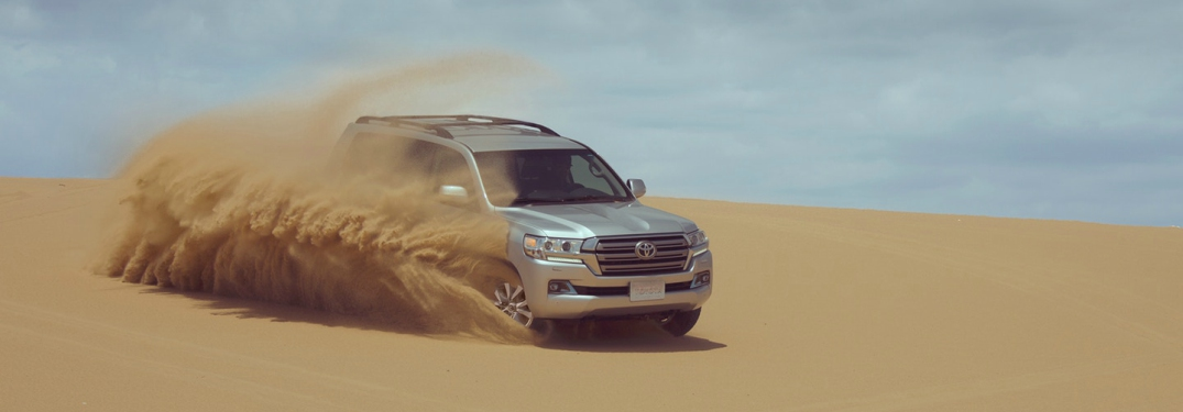 silver 2018 Toyota Land Cruiser driving in the sand
