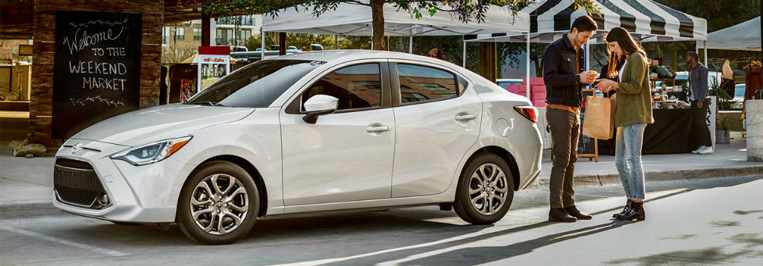 2019 Toyota Yaris exterior front fascia and drivers side at outdoor market with young couple