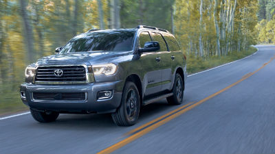 2019 Toyota Sequoia exterior front fascia and drivers side with blurred trees on road going fast