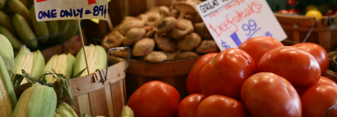 tomatoes corn and mushrooms at farmers market with signs