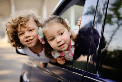 two children hanging out of car window