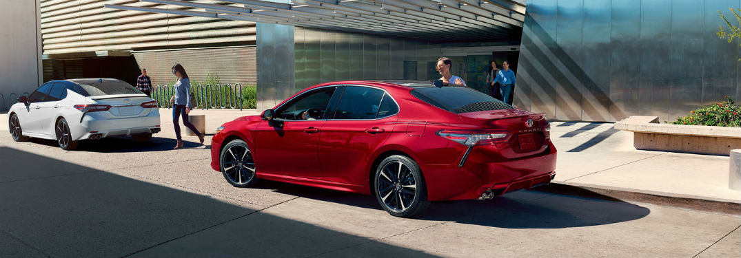 2019 Toyota Camry exterior back fascia drivers side parked behind 2nd Camry people on sidewalk