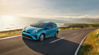 2019 Toyota Prius c exterior front fascia and drivers side on road next to water