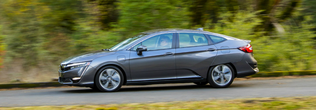 2018 Honda Clarity Plug-In Hybrid driving down a road in the woods